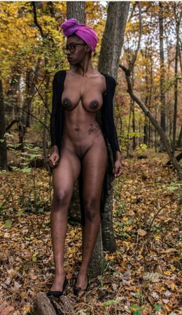Tall ebony model with tattoos posing..